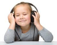 Fille mignonne appréciant la musique utilisant des écouteurs Images stock