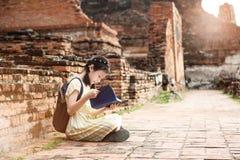Fille mignonne asiatique détendant dehors tandis que livre d'histoire lu, Studen photographie stock libre de droits