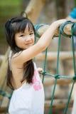 Fille mignonne asiatique heureuse jouant sur le terrain de jeu Images stock