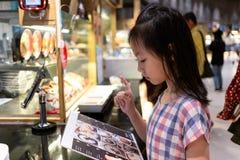 Fille mignonne asiatique passant commande du menu photos libres de droits