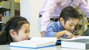 Fille mignonne asiatique reposant et voyant l'ami badiner lire la BO Photos stock