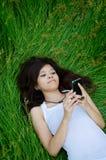Fille mignonne asiatique texting sur le pré image stock