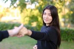 fille mignonne aux cheveux noirs se tenant à la main de type de longueur du ` s de bras, souriant Photographie stock libre de droits
