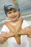 Fille mignonne avec des étoiles de mer sur la plage photo stock