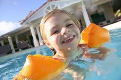 Fille mignonne avec des brassards nageant dans la piscine Images libres de droits