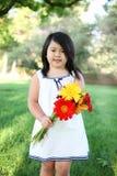 Fille mignonne avec des fleurs Photographie stock