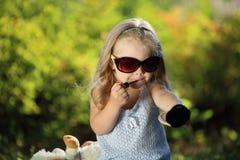 Fille mignonne avec des lunettes de soleil appliquant dehors le lustre de lèvre Photographie stock