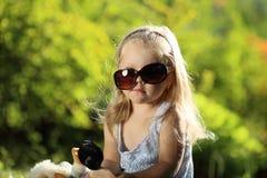 Fille mignonne avec des lunettes de soleil dehors Photos libres de droits