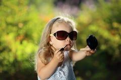 Fille mignonne avec des lunettes de soleil dehors Images libres de droits