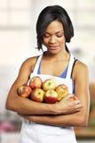 Fille mignonne avec des pommes dans la cuisine images libres de droits