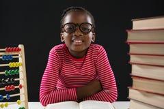 Fille mignonne avec l'abaque et la pile de livres Photographie stock libre de droits