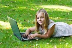 Fille mignonne avec l'ordinateur portable sur l'herbe verte Image stock