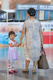 Fille mignonne avec la grand-mère attendant à l'aéroport international capital de Pékin Photos libres de droits