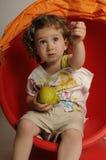 Fille mignonne avec la poire se reposant sur la chaise rouge Photos libres de droits