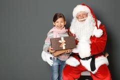 Fille mignonne avec le boîte-cadeau et la Santa Claus authentique sur le fond gris image stock