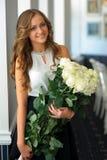 Fille mignonne avec le sourire de bouquet de fleurs blanches Images stock