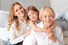 Fille mignonne avec plaisir étreignant sa grand-mère Photographie stock libre de droits
