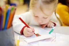 Fille mignonne d'élève du cours préparatoire dessinant une photo Photo stock