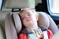 Fille mignonne d'élève du cours préparatoire dormant dans la voiture image stock