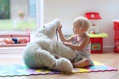 Fille mignonne d'élève du cours préparatoire jouant le jeu de docteur avec ses jouets Image stock