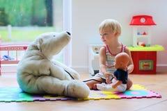 Fille mignonne d'élève du cours préparatoire jouant le jeu de docteur avec ses jouets Image libre de droits