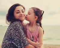 Fille mignonne d'enfant embrassant sa mère appréciante heureuse avec les yeux fermés Images stock
