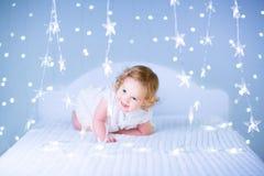 Fille mignonne d'enfant en bas âge avec les cheveux bouclés entre les lumières de Noël Image libre de droits