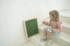 Fille mignonne d'enfant en bas âge dans l'écriture attachée de tête argentée sur le tableau noir de craie, séance Photo stock