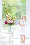 Fille mignonne d'enfant en bas âge en fleurs de arrosage de robe blanche Image stock