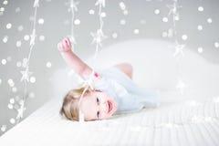 Fille mignonne d'enfant en bas âge jouant sur un lit entre les lumières de Noël Images stock