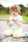 Fille mignonne d'enfant en bas âge regardant ses mains sales photos libres de droits