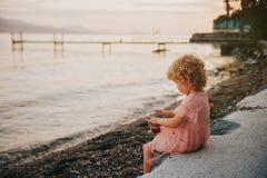 Fille mignonne d'enfant en bas âge se reposant par le lac photos stock