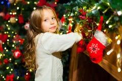 Fille mignonne d'enfant en bas âge vérifiant son bas de Noël sous un beauti Images stock
