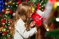 Fille mignonne d'enfant en bas âge vérifiant son bas de Noël sous un beauti Photo stock