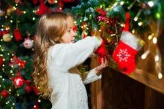 Fille mignonne d'enfant en bas âge vérifiant son bas de Noël sous un beauti Photos stock