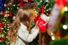Fille mignonne d'enfant en bas âge vérifiant son bas de Noël sous un beauti Photos libres de droits