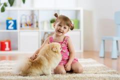 Fille mignonne d'enfant s'asseyant sur le plancher avec son chien Image stock