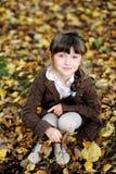 Fille mignonne d'enfant s'asseyant sur le tapis des lames d'automne Images stock