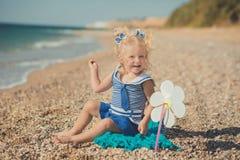 Fille mignonne d'un côté de mer avec deux étoiles de mer dans la robe bleue Photos libres de droits