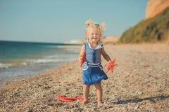 Fille mignonne d'un côté de mer avec deux étoiles de mer dans la robe bleue Photos stock