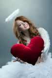 Fille mignonne dans le costume d'ange posant avec le coeur de nounours Image stock