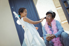Fille mignonne dans le costume féerique mettant le maquillage sur son visage de pères Photographie stock
