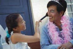 Fille mignonne dans le costume féerique mettant le maquillage sur son visage de pères Images stock