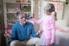 Fille mignonne dans le costume féerique mettant le maquillage sur son visage de pères Image libre de droits
