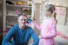 Fille mignonne dans le costume féerique mettant le maquillage sur son visage de pères Photos libres de droits