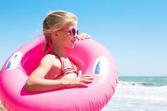 Fille mignonne dans le maillot de bain jouant avec un anneau gonflable sur l'océan images stock