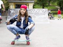 Fille mignonne dans une casquette de baseball avec une planche à roulettes en parc de patin sports Image stock