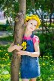 Fille mignonne dans une guirlande des pissenlits tenant un bouquet des pissenlits dans ses supports de main embrassant un tronc d photographie stock