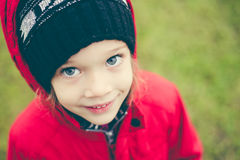 Fille mignonne dans une veste et un chapeau sur le stree Photos stock