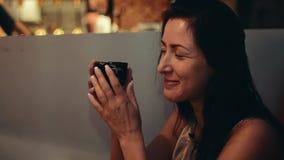 Fille mignonne de brune à la table dans le restaurant rire thé de boissons Parlez à quelqu'un banque de vidéos